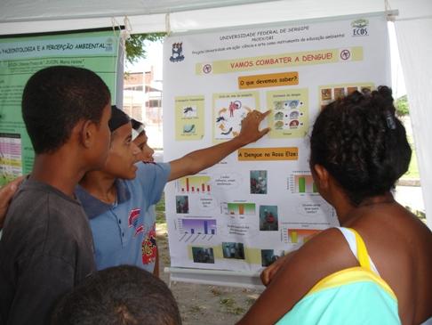 Aluno do Clube de Ciências apresenta seu painel para moradores do Rosa Elze