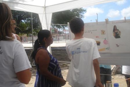 Arlisson, aluno do projeto, apresentando material para a moradora do bairro
